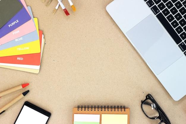 ノートパソコン、スマートフォン、本、消耗品を備えた木製のオフィスデスクテーブル。コピースペース、フラットレイの上面図。