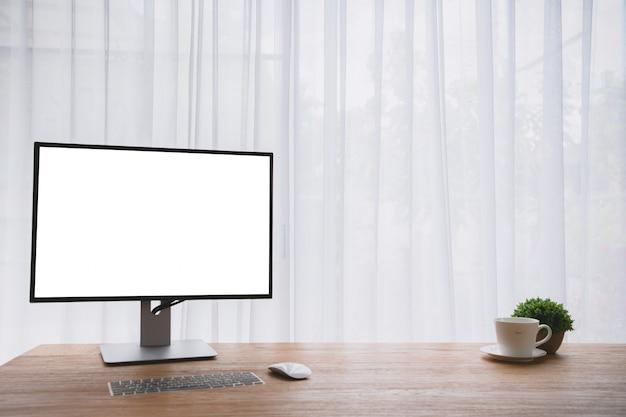 Деревянная таблица офиса с пустым экраном на экране компьютера монитора и кофейной чашке.