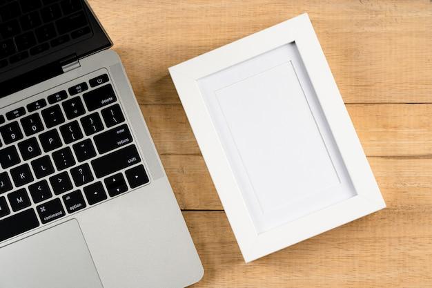 노트북 및 빈 그림 프레임, 작은 식물, 연필 나무 사무실 작업 공간 책상 테이블. 복사 공간 평면도, 평평하다.