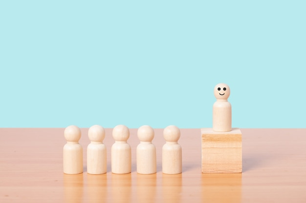 Деревянная модель человека стоя на подиуме среди людей на синем фоне. концепция лидерства.