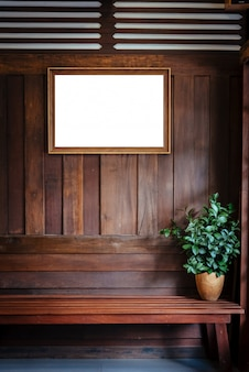 Wood picture frame hang on wood wall background with plant vase on chair.