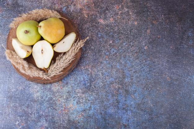 大理石の背景に熟した緑の梨と木片。