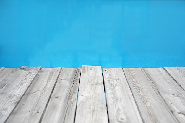 Wood plank pier against blue water