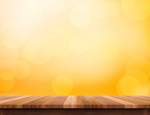 Wood plank table top at orange bokeh light background