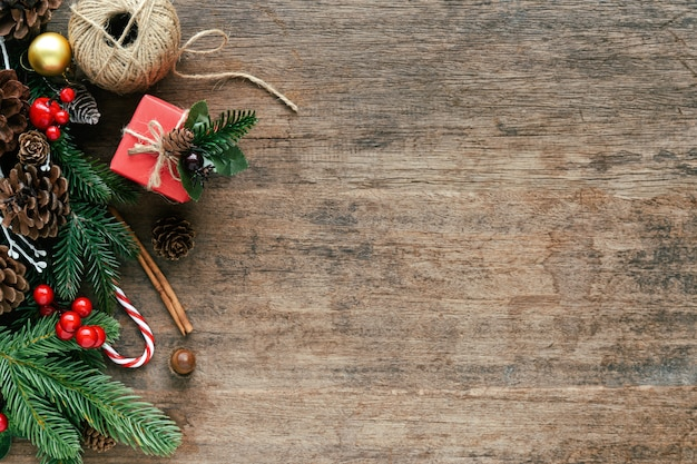 Wood plank with pine leaves, pine cones, holly balls, gift box and candy cane in christmas concept.