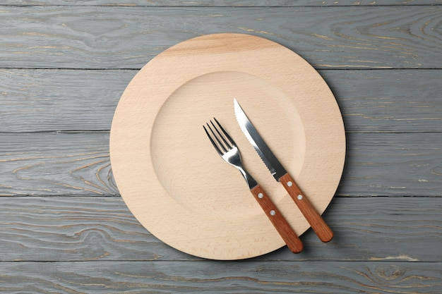 Wood plate, knife and fork on wooden background, top view