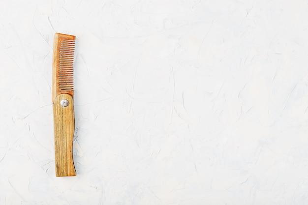 Древесина сандал расческа складная на белой фактурной.