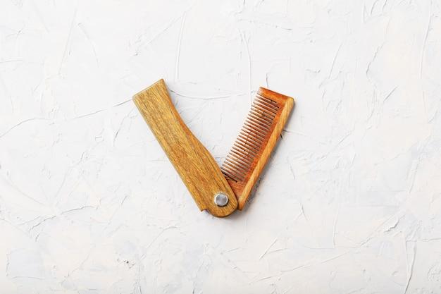 Wood sandalwood comb folding on white textured.