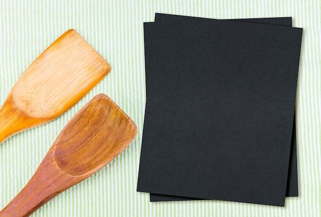 ブランク黒のメニュー用紙と緑のテーブルクロスの上に木のスプーン