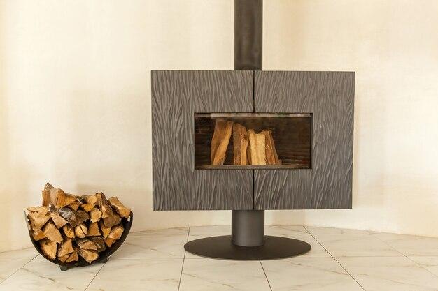 Дровяная печь-камин. современная дровяная печь-камин прикручена к полу, с длинной трубой и дровами внутри.