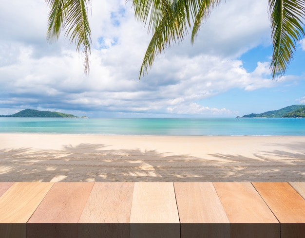 Деревянный стол и пляж, морской песок и пальмы в летний день