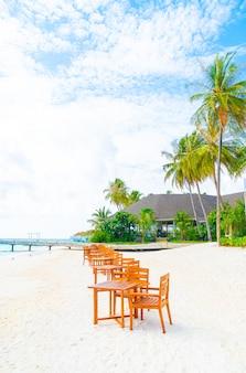 Деревянный стол и стул на пляже с фоном с видом на море на мальдивах