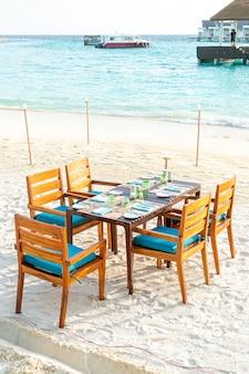Деревянный стол и стул на пляже с видом на море на мальдивах
