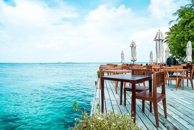 Деревянный стол и стул с фоном с видом на море на мальдивах