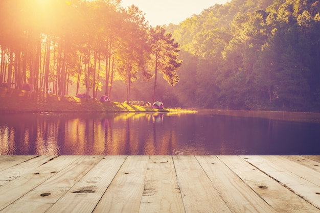 Деревянный стол и вода из пруда и восход солнца с винтажным эффектом.