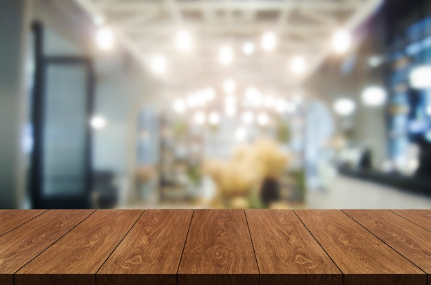 Wood table in blurry background of modern restaurant room or coffee shop for product display mockup.