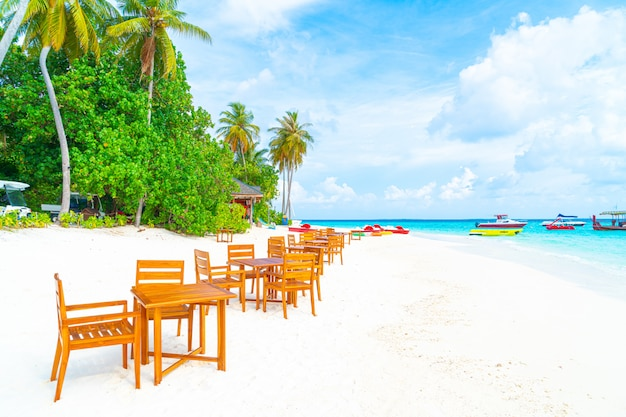 Wood table and chair on beach with sea view background in maldives