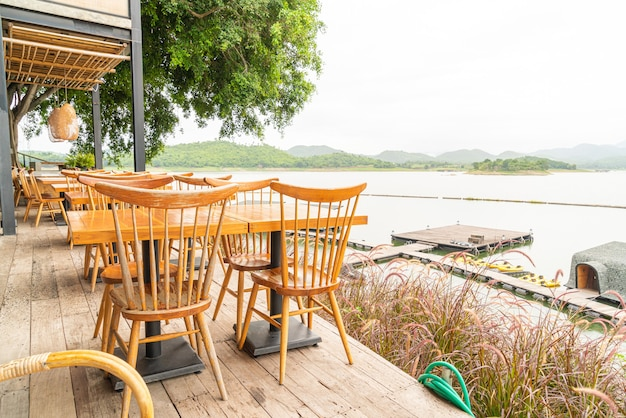 Wood table and chair in cafe restaurant by a lake