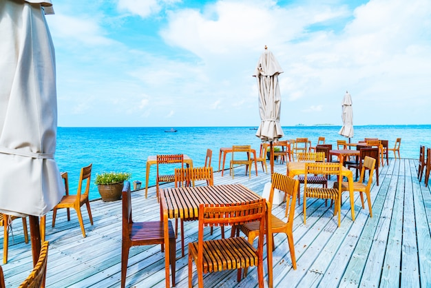 Wood table and chair with sea view background in maldives