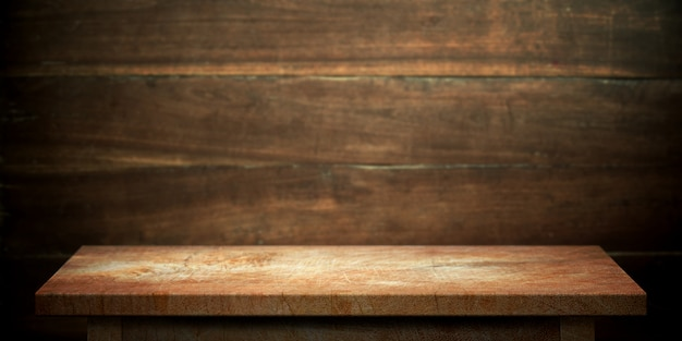 Wood table on dark brown wall blurred background.