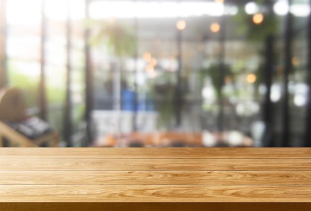 현대적인 레스토랑 룸 또는 제품 디스플레이 모형을위한 커피 숍의 흐린 배경에 나무 테이블