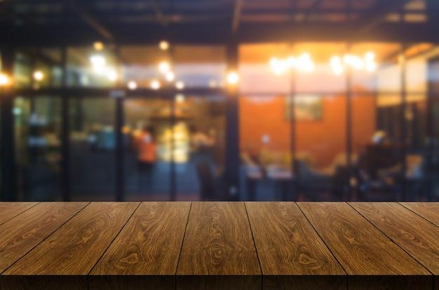 Деревянный стол на размытом фоне современного ресторанного зала или кафе для макета дисплея продукта