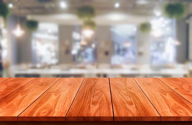Деревянный стол на размытом фоне современного ресторанного зала или кафе для макета дисплея продукта.