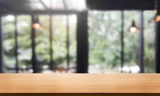 Деревянный стол в размытом современном ресторане или кафе для макета дисплея продукта.