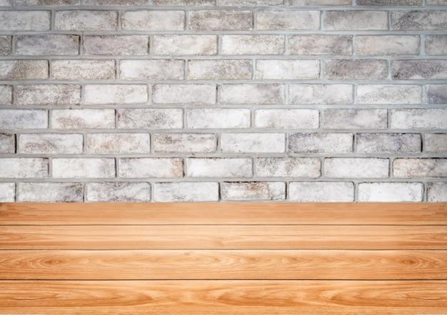 Деревянный стол перед деревенской кирпичной стеной размытия фона с пустым пространством для копии на столе.