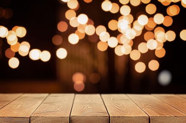 전경에 있는 나무 테이블과 배경에 금색 디포커스 조명, 복사 공간이 있는 배경