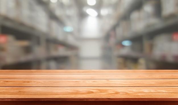 Деревянный стол в размытии складского хранения с пустым пространством для копии на столе для отображения продукта.