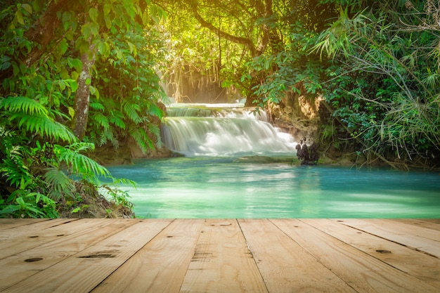 Wood table and kuang si waterfalls in luang prabang, laos.
