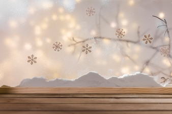 Wood table near bank of snow, plant twig, snowflakes and fairy lights