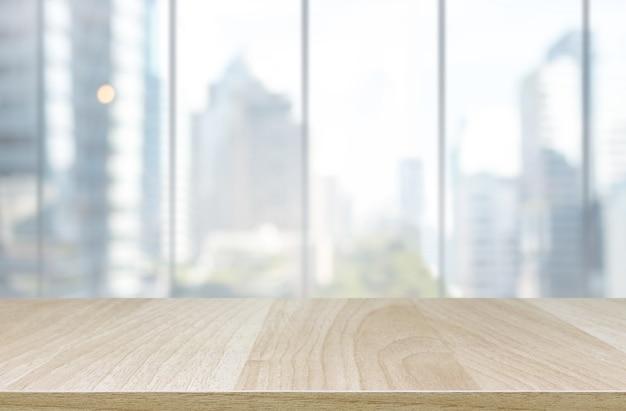 나무 테이블 상단 및 흐림 유리 창 벽 건물 배경-디스플레이에 사용하거나 제품을 몽타주 할 수 있습니다.