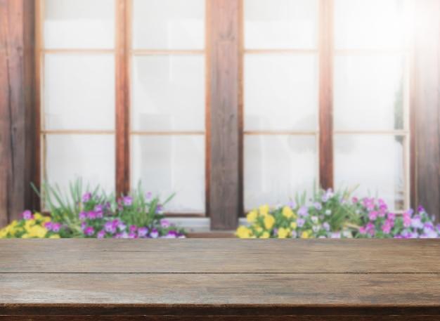 빈티지 필터 나무 테이블 상단과 흐린 꽃과 창 배경