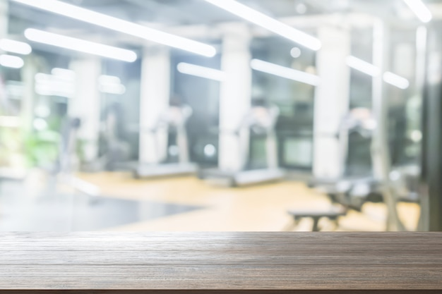 Wood table top background on blurred fitness gym