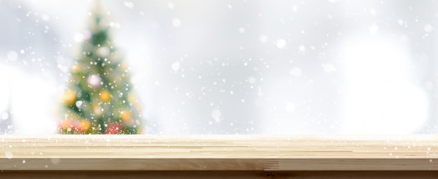 Wood table top on blur christmas tree banner background