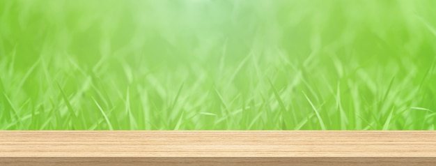 Wood table top and blur green grass for product and display montage banner size.