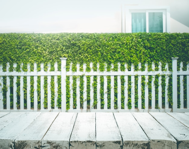 Wood table top on blur of white fence and garden background