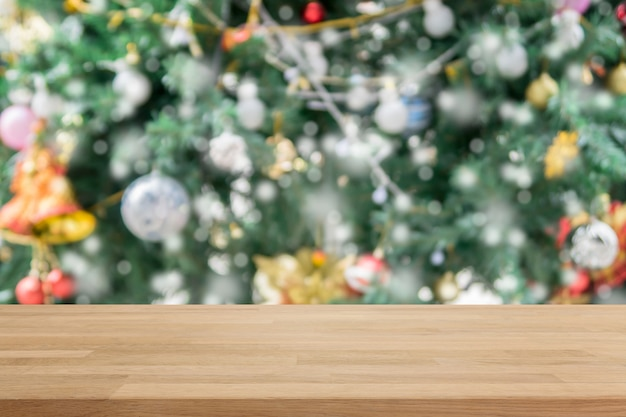 Wood table top on blur with bokeh christmas tree background with vintage filter - can be used for display or montage your products