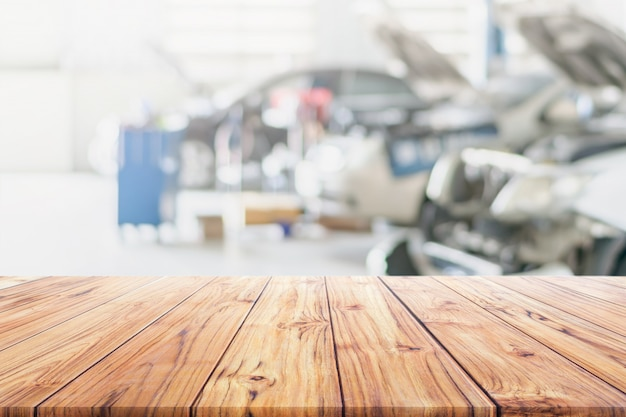 Wood table top on blurred car repair services center