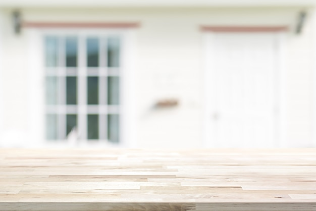 Wood table top on blurred white house front with door and glass window