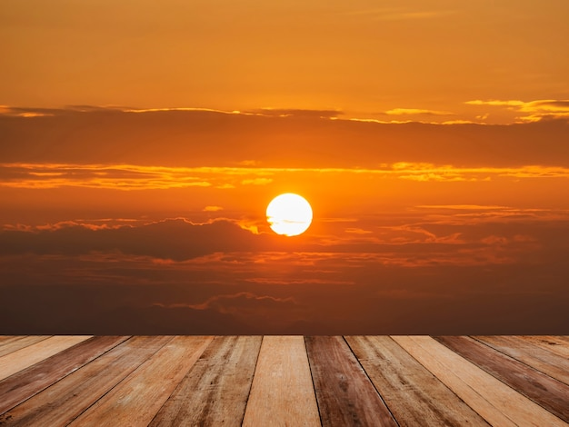 Wood table top over bright sun and dramatic sunrise clouds sky.
