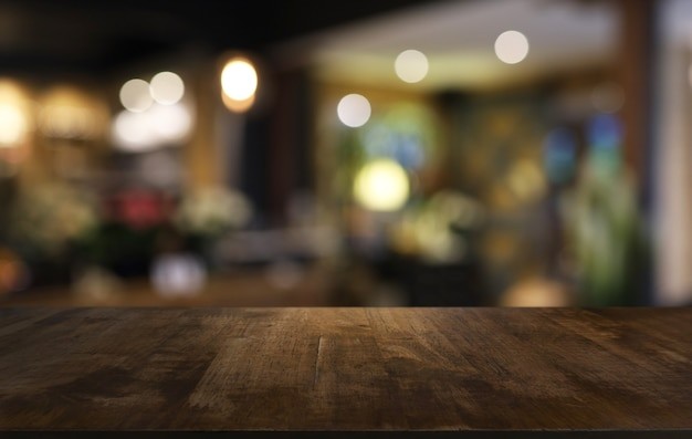 ぼかしの背景の木製テーブルトップ空のコピースペースのある部屋のインテリア