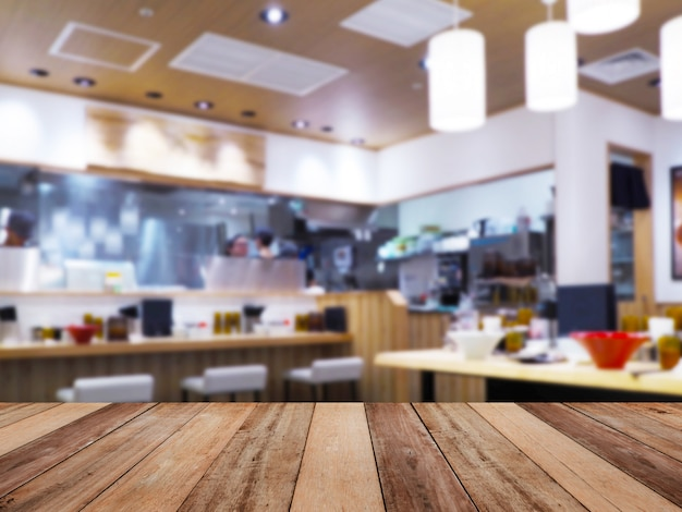 Wood table top over noodle restaurant blur background.