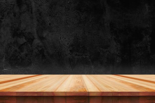むき出しのコンクリート壁の背景にある木製のテーブルトップ-製品の展示やモンタージュに使用できます