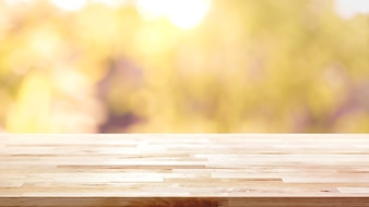 Wood table top on blur abstract natural foliage bokeh background, vintage tone