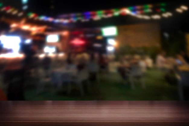 ぼやけた夜のパーティーの背景に木製のテーブルトップ
