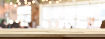 Wood table top on blur restaurant or cafe interior banner background