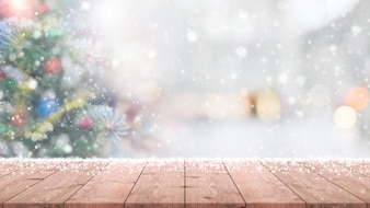 Wood table top on blur with bokeh christmas tree background with snowfall